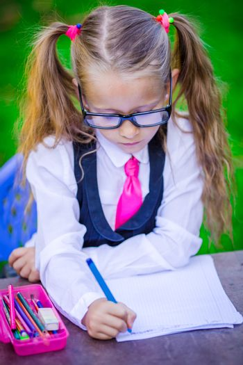 Clever little school girl at desk with notes and pencils outdoor. Back to school.