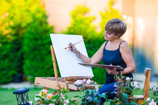 Happy woman painting picture of an floral landscape in spring time