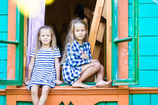 Adorable little girls in the window of rural house outdoors