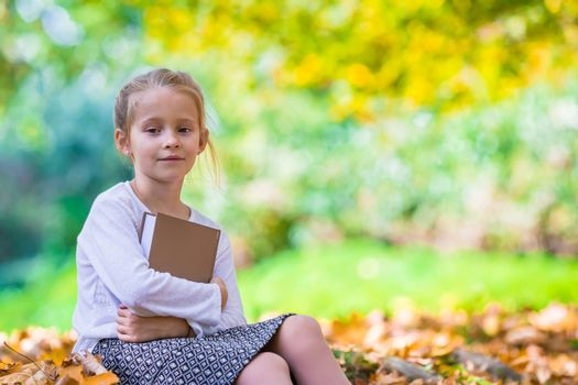 Adorable little clever girl with book in beautiful autumn dau outdoors