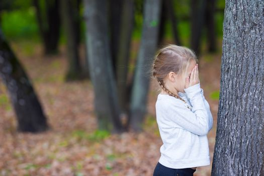 Cute girl playing hide and seek near tree in autumn park