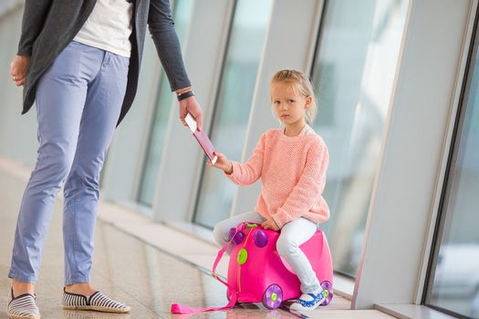 Happy family with boarding pass and luggage at airport waiting for boarding