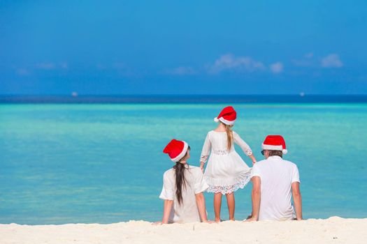 Young couple with little daughter in Santa hats relaxing on tropical beach during Christmas vacation