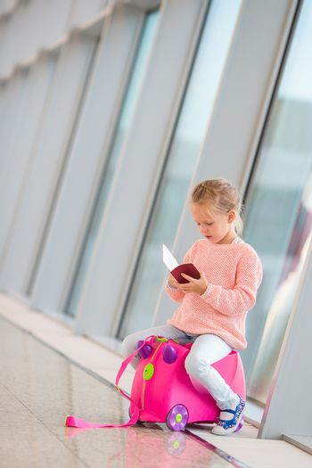 Adorable little girl with boarding pass and luggage in airport waiting for boarding