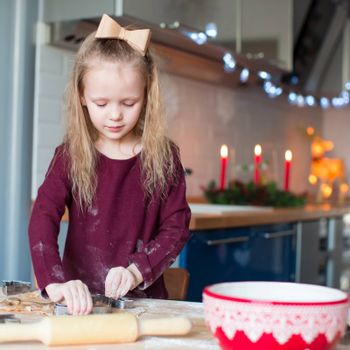Happy adorable girl baking Christmas cookies at home