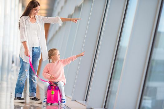 Happy family at airport sitting on suitcase with boarding pass waiting for boarding