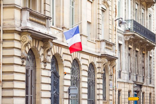 French flag at facade of historic building in Paris