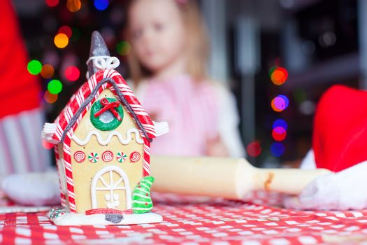 Gingerbread fairy house for Christmas on background of kids and fir-tree with garland