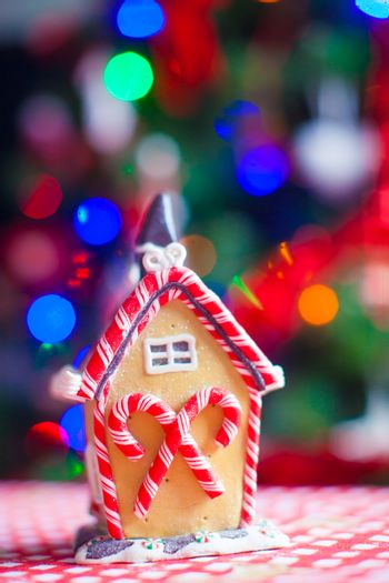 Gingerbread fairy house on a background of bright Christmas tree with garland