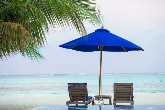 Beach chairs on exotic tropical white sandy beach in Indian Ocean