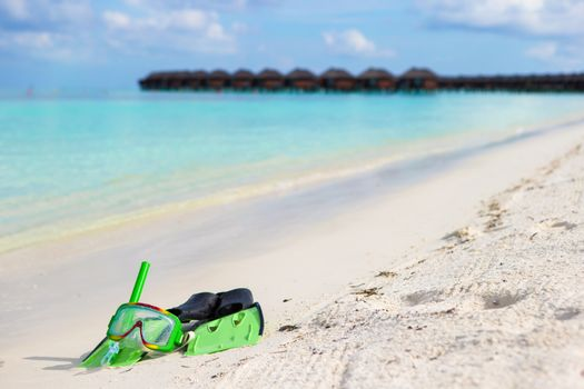 Mask, snorkel and fins for snorkeling on white sandy beach
