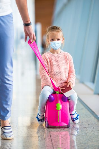 Little adorable kid with surgical mask face protection at international airport. Father and little daughter with boarding pass at airport terminal ready for vacation
