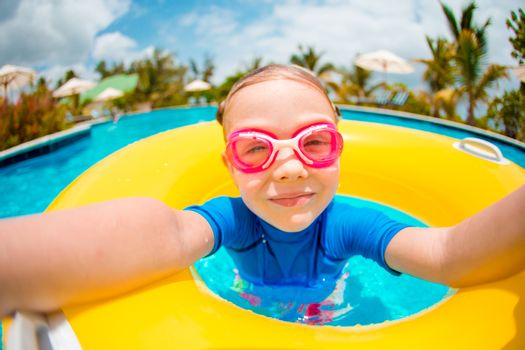 Portrait of cute girl with inflatable rubber ring having fun in swimming pool