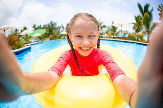 Little girl making selfie at inflatable rubber ring having fun in swimming pool