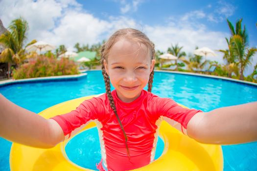 Little girl making selfie at inflatable rubber ring in swimming pool