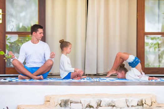 Young family meditating on the terrace