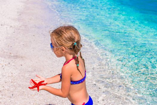Little adorable girl with starfish in hands at the tropical beach