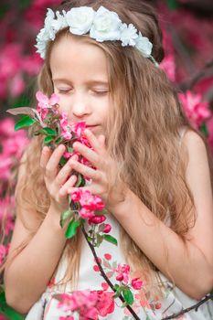 Adorable little girl enjoying smell in a flowering spring garden
