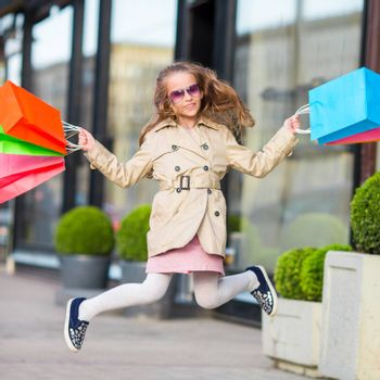Adorable smiling little girl with shopping bags outdoors