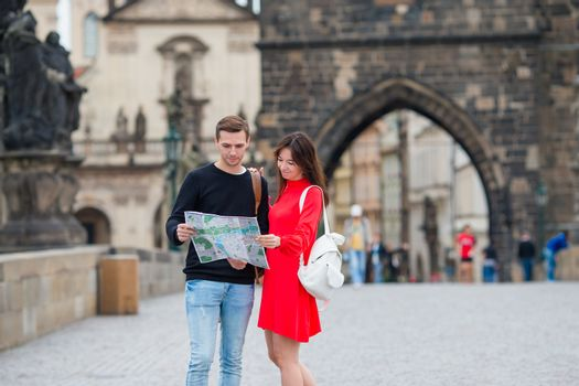 Happy tourist couple traveling on Charles Bridge in Prague at famous places with city map