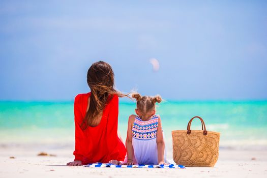 Mother and daughter enjoying time at tropical beach. Happy family with straw bag on summer holidays