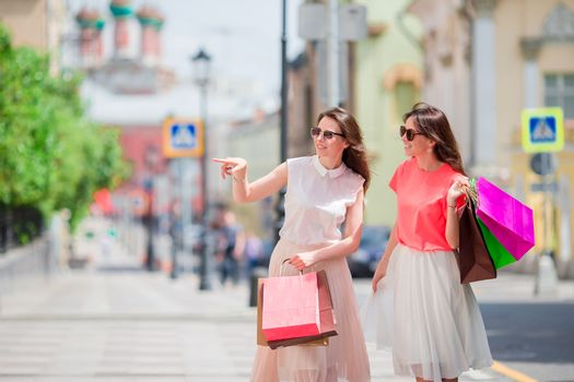 Happy young women with shopping bags enjoy their day walking along city street. Sale, consumerism and people concept.