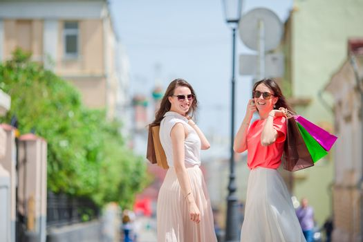 Happy young women with shopping bags walking along city street. Sale, consumerism and people concept.