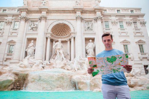 Young man with touristic citymap near Fountane di Trevi, Rome, Italy.
