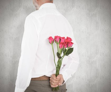 Man holding bouquet of roses behind back against weathered surface