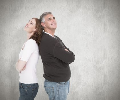 Casual couple smiling and looking up against white background