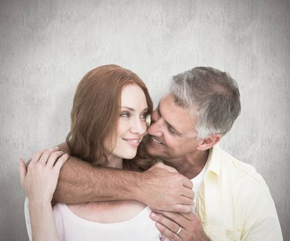 Casual couple smiling and hugging against white background