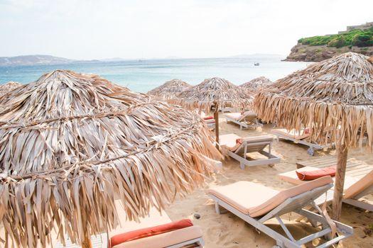 Sun beds and umbrellas on the sandy beach near the sea in Greece