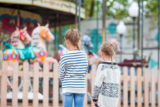 Adorable little girls near the carousel outdoors