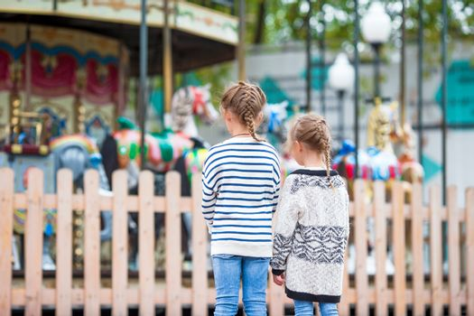 Adorable little girls near the carousel in the kids park outdoors