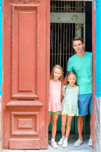 Portrait of happy family looking out door at old apartments in Havana