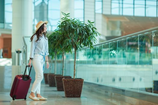 Young woman in hat with luggage in international airport. Airline passenger in an airport lounge waiting for flight aircraft
