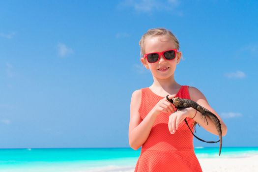 Adorable little girl happily holds a wild tropical lizard