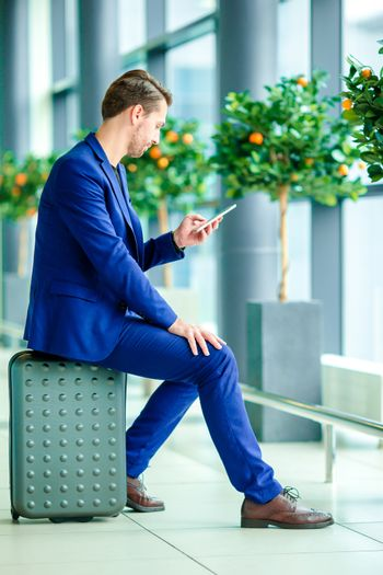 Urban businessman talking on smart phone inside in airport. Casual young man with cellphone at the airport while waiting for boarding