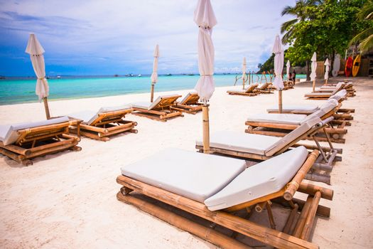 Beach beds and umbrellas on exotic tropical white sandy beach
