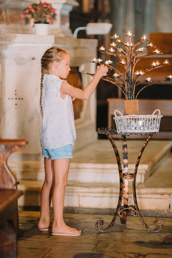 Little girl in church with candles indoor