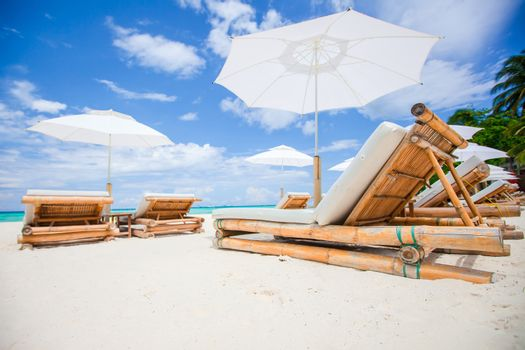 Beach beds and white umbrellas on exotic tropical white sandy beach