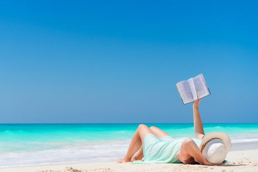 Woman with book on the seashore lying