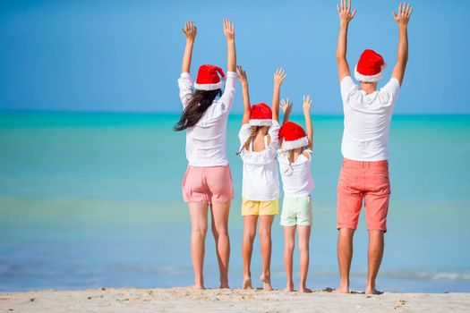 Happy family with two kids on Christmas on the beach