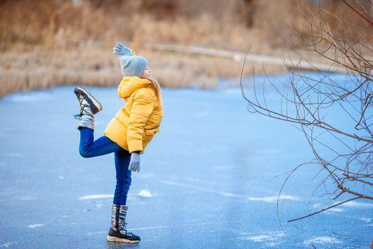 Adorable little girl having fun on frozen lake in winter