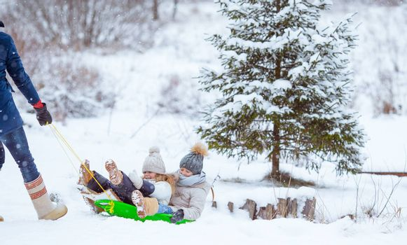 Family of dad and kids vacation on Christmas eve outdoors sledge and have fun in winter day