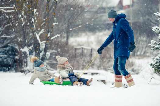 Little girls enjoy a sleigh ride. Kids sledding. Children play outdoors in snow. Family vacation on Christmas eve outdoors