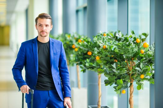 Portrait of young man in airport with baggage