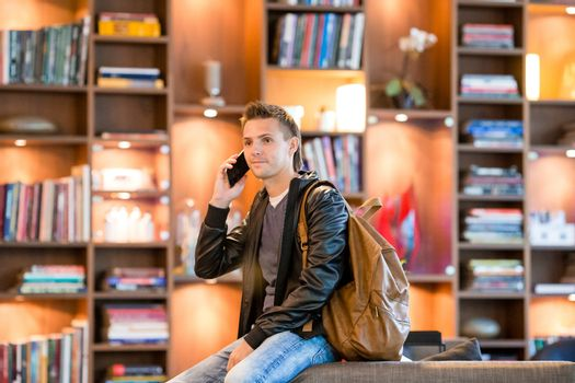 Young man taking by smartphone in bookstore
