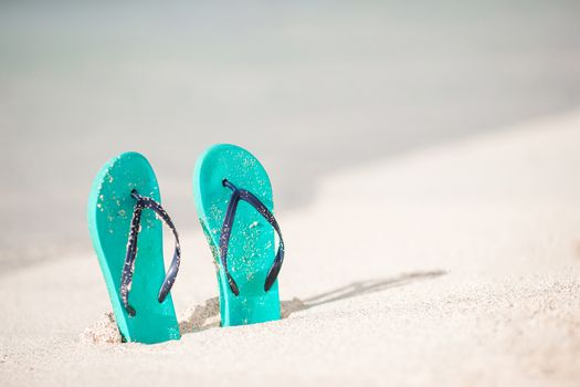 Summer mint flipflops with sunglasses on white beach