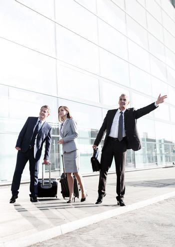 Business people calling for taxi in the airport